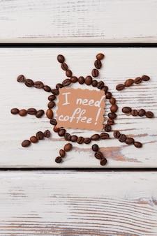 Zon gemaakt van koffiebonen op witte houten planken. ik heb koffie nodig.