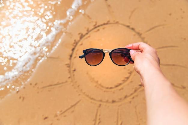 Zon geschilderd op het zand met zonnebril