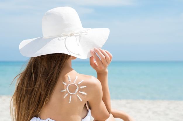 Zon getrokken met zonnebrandcrème vrouw schouder