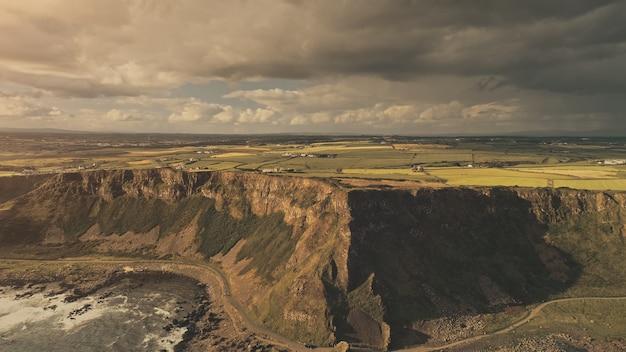 Zon oceaan baai kust luchtfoto niemand natuur landschap klif gras vallei boerderijen op platteland landelijk