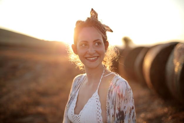 Zon schijnt over een glimlachende vrouw die op een veld staat