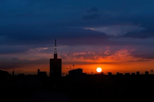 Zon stijgt boven de stad, dak bovenaanzicht van een oude kerktoren.