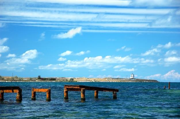 Zon stijgt boven horizon en pier, strand verlicht met zonlicht, zwarte zee