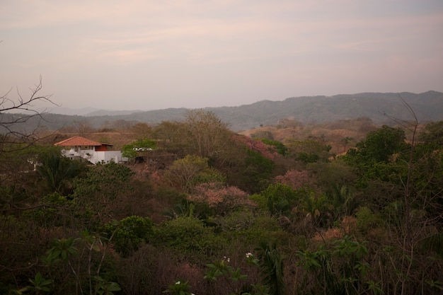 Zon vervaagt over een wit huis met een oranje dak in de glooiende heuvels boven de boomtoppen van costa rica