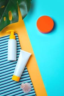 Zonbescherming, sanscreen-producten. minimaal concept van zomervakantie, zonnebank. plat leggen, natuurlijke cosmetica, crème met spf voor gezicht en lichaam. preventie van fotoveroudering.
