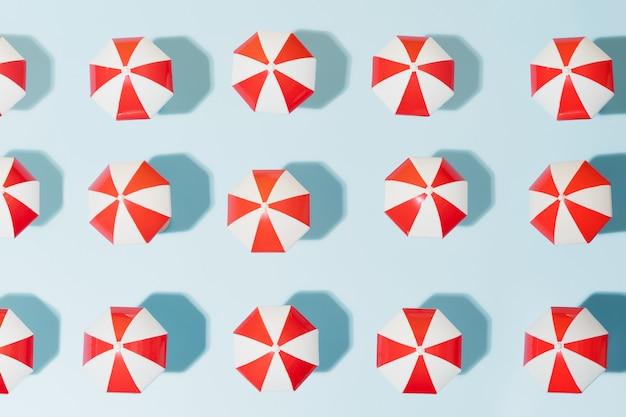 Zonbeschermingsparaplu voor strand in rood en wit op een blauwe achtergrondparasol voor buiten zomervakantie concept bovenaanzicht