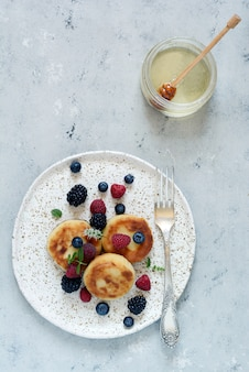 Zondag ontbijt met cheesecake, honing, verse bessen en munt