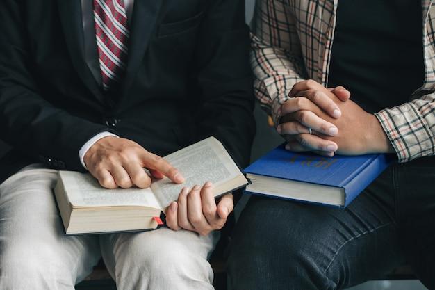 Zondaglezingen, twee mannen lezen en studeren samen de bijbel in huis of zondagsschool in de kerk met raamlicht