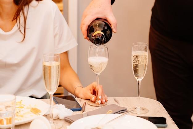 Zonder gezichten schenkt een man champagne in damesglazen