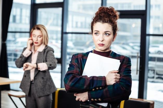 Zonder jobaanbieding. jonge stagiair met donker haar en krullen verlaat het bedrijf zonder baanaanbieding