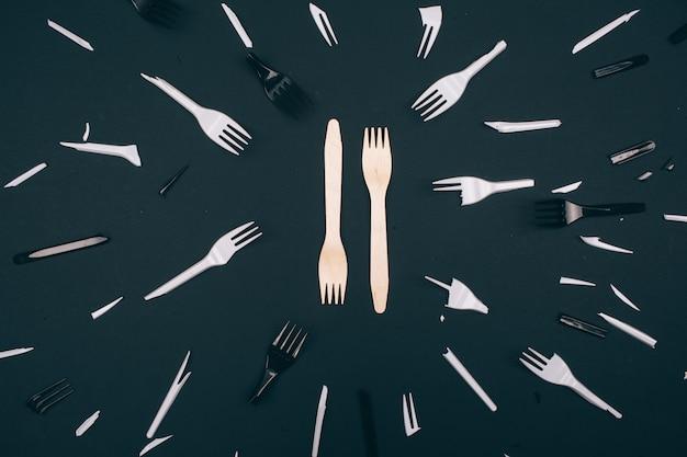 Zonder plastic. geen afvalconcept. milieuvriendelijke ongebroken vorken in het midden van gebroken witte en zwarte vorken voor eenmalig gebruik op een donkere achtergrond. kies plastic voor eenmalig gebruik of natuurlijk recyclebaar product.