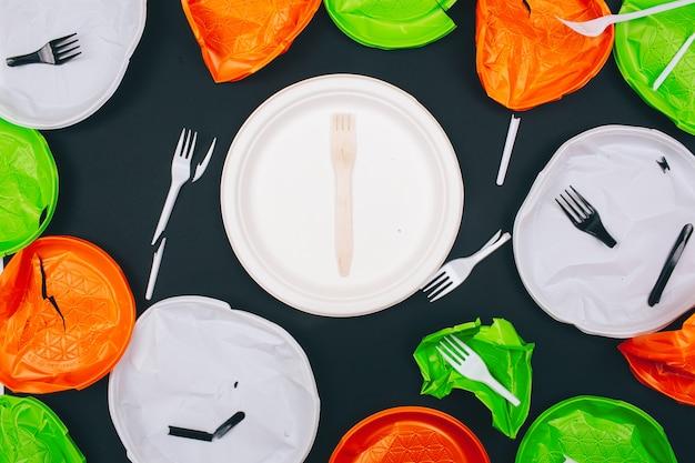 Zonder plastic. houten ongebroken plaat en vork in het centrum van wegwerp gebroken plastic platen en vorken op donkere achtergrond, bovenaanzicht. kunststof voor eenmalig gebruik, eu-europese richtlijn om het milieu te helpen.