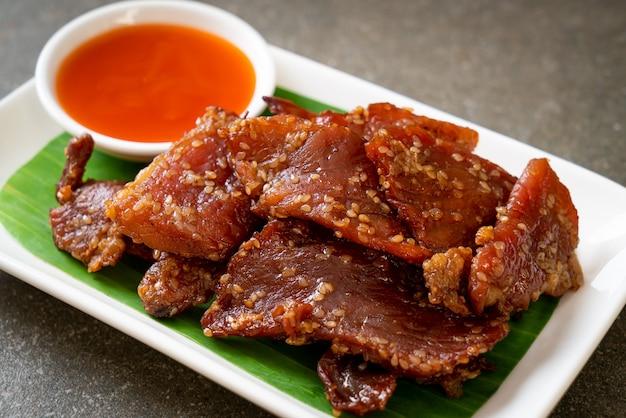 Zongedroogd varkensvlees met saus op bord