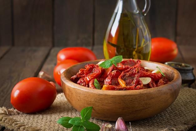 Zongedroogde tomaten met kruiden en knoflook in houten kom