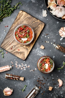 Zongedroogde tomaten met verse kruiden en specerijen, zeezout in olijfolie in een glazen pot