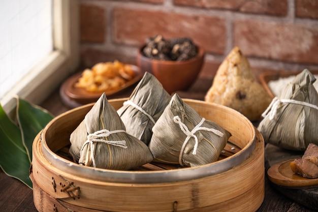 Zongzi chinese rijstbol zongzi in een stoomboot op houten tafel voor dragon boat festival