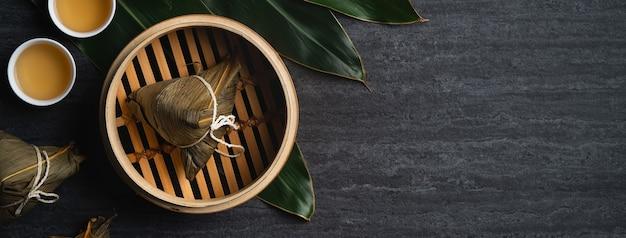 Zongzi rijst knoedel bovenaanzicht voor chinese traditionele dragon boat festival (duanwu festival) over donkere zwarte leisteen achtergrond