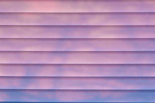 Zonlicht dat door jaloezieën bij het raam komt