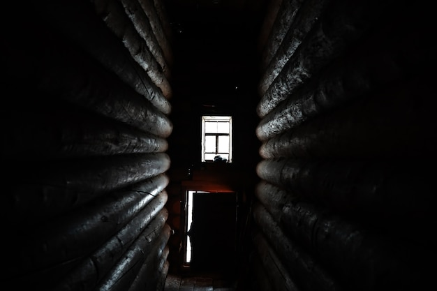 Zonlicht komt door het houten raam in een oude donkere kamer
