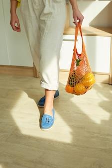 Zonlicht met bovenaanzicht van vrouw in groene schoenen met string kruidenier herbruikbare netzak vol met verse groenten en fruit thuis concept van winkelen en gezond veganistisch eten zero waste