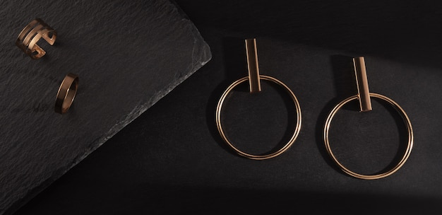 Zonlicht op gouden oorbellen paar en ringen op zwarte steen achtergrond. bovenaanzicht van moderne gouden accessoires op zwarte stenen achtergrond.