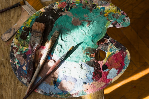 Zonlicht op rommelige palet en penseel over houten tafel
