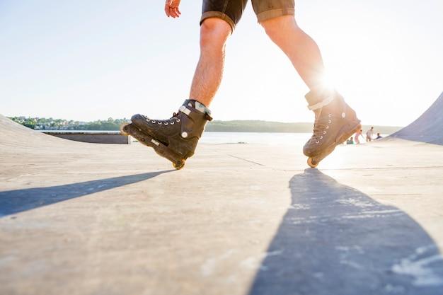 Zonlicht over de persoon rolschaatsen in skatepark