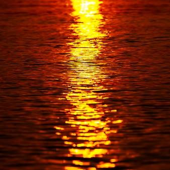 Zonlicht reflecteert op zee-oppervlak in de ochtend