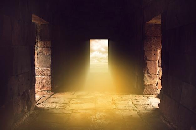 Zonlicht schijnt door de deur aan het einde van een oude stenen tempel, reis in een mysterieus land.