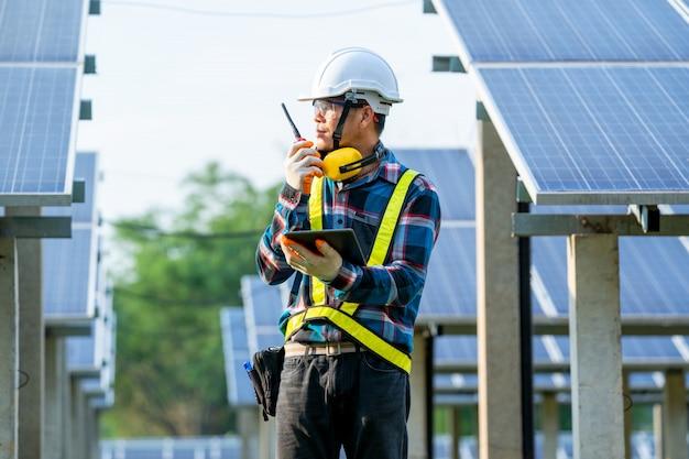 Zonne-energiecentrale, ingenieur bezig met controle en onderhoud in zonne-energiecentrale van fotovoltaïsche panelen, wetenschap zonne-energie.