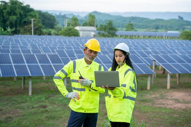 Zonne-energiecentrale, ingenieur werken met tabletcomputer op zonnepanelen.