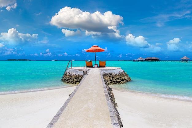 Zonnebank en parasol op tropisch strand in de malediven