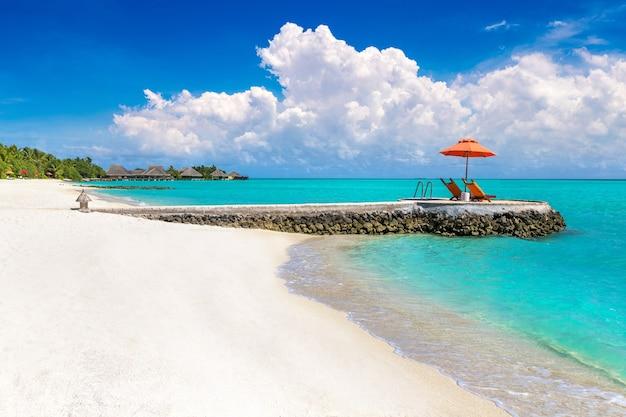 Zonnebank en parasol op tropisch strand op de malediven