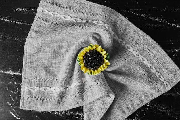 Zonnebloem cupcake op een keukenhanddoek.