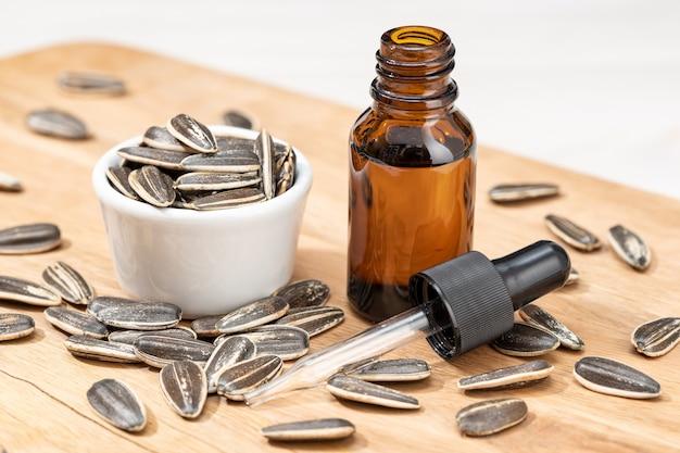 Zonnebloem etherische olie in glazen fles met pipet op houten tafel