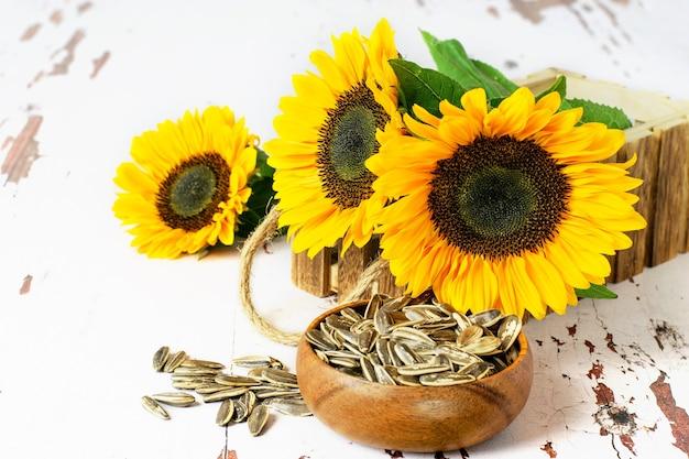 Zonnebloemen in de rustieke houten doos, zonnebloempitten in de kom, op de witte vintage achtergrond.