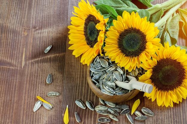 Zonnebloemen met groene bladeren en stengels op de houten achtergrond. zonnebloempitten in de houten kom.