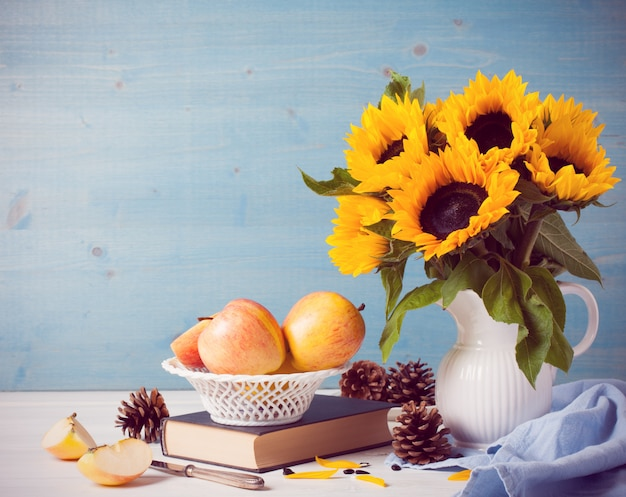 Zonnebloemenboeket in witte vaas met appelen