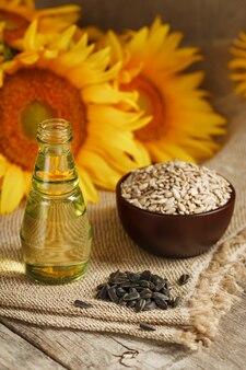 Zonnebloemolie in een fles met zonnebloempitten en bloemen op hout