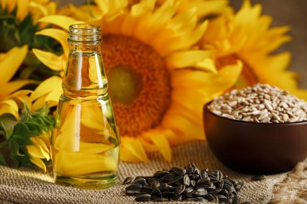 Zonnebloemolie met zonnebloempitten en bloemen op hout