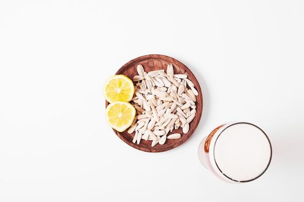 Zonnebloempitten en bier op wit.