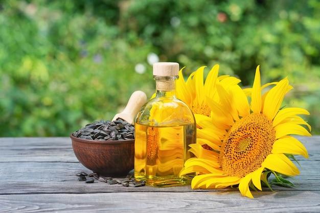 Zonnebloempitten en bloemen met een fles olie op een houten tafel