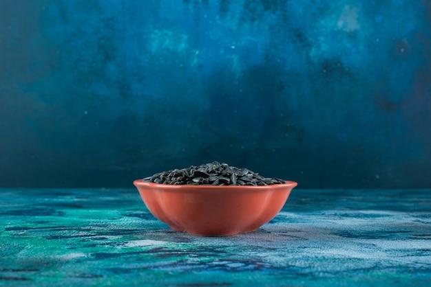 Zonnebloempitten in een kom, op de marmeren tafel.