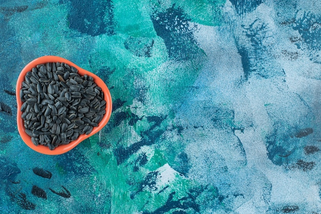 Zonnebloempitten in een kom op marmer.