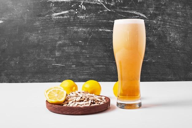 Zonnebloempitten met citroen en bier op wit.