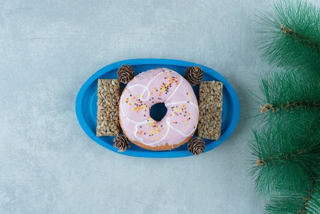Zonnebloempitten snackbars en een donut met dennenappels op een schaal naast een kunstmatige dennentak op marmer.
