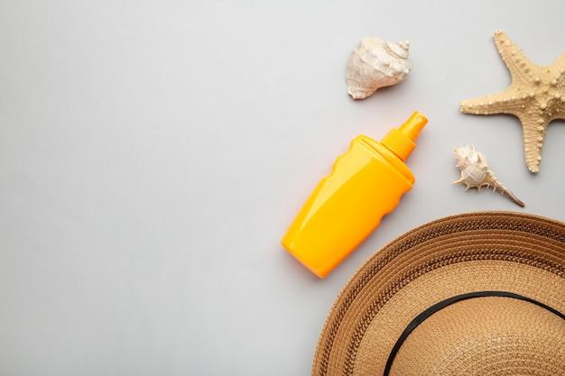 Zonnebrandcrème fles met andere accessoires op grijze achtergrond