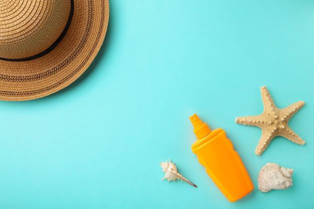 Zonnebrandcrème fles met hoed en schelpen op blauwe achtergrond