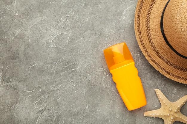 Zonnebrandcrème fles met hoed en schelpen op grijze achtergrond