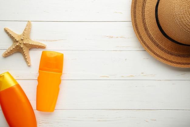 Zonnebrandcrème fles met hoed en schelpen op witte achtergrond